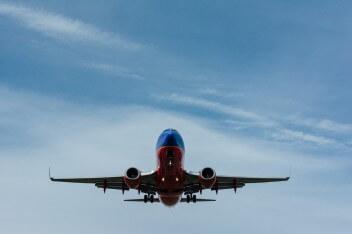 в небе летит яркий самолёт